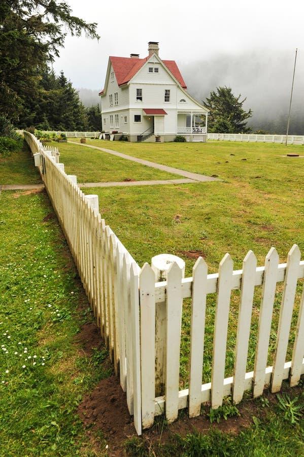 Il faro tiene la casa circondata dal recinto immagine stock libera da diritti