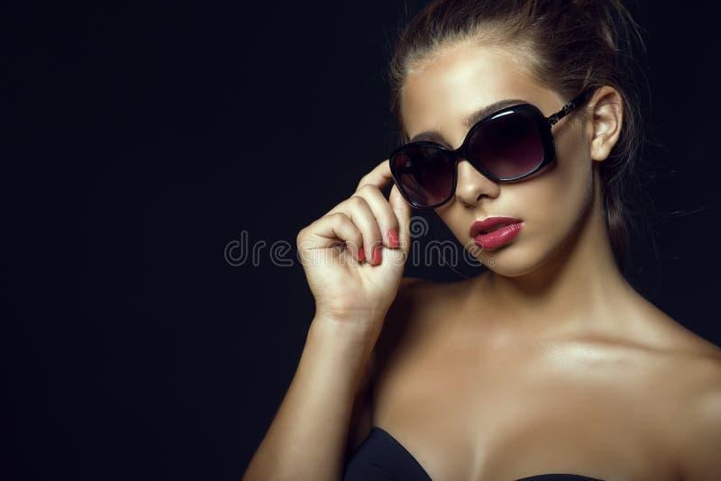 Il fascino splendido ha abbronzato il modello che indossa gli occhiali da sole classici d'avanguardia fotografia stock