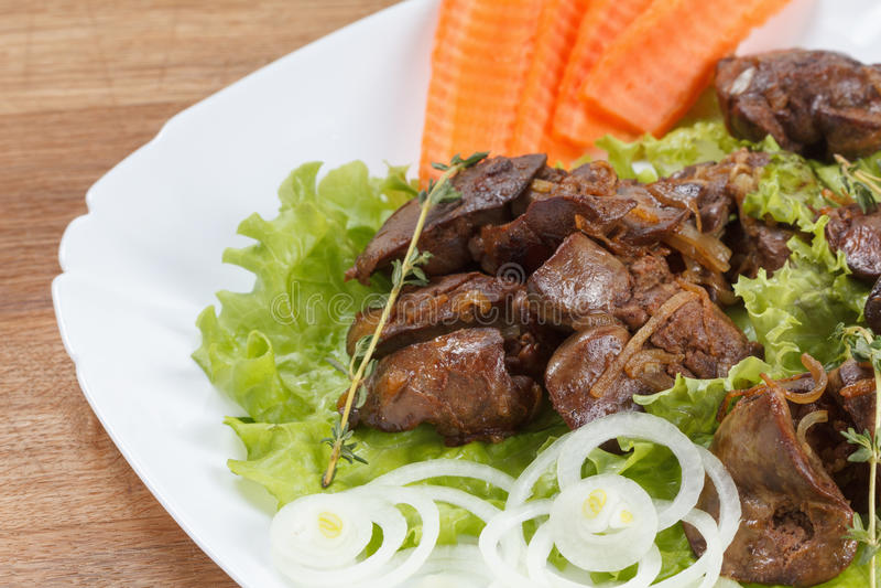 Il fegato di pollo ha cucinato con le cipolle, la lattuga e le spezie fotografia stock