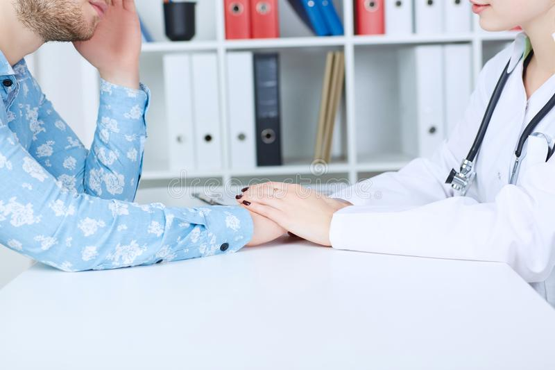 Il ` femminile amichevole s di medico passa a tenuta la mano paziente maschio del ` s per incoraggiamento e l'empatia Fiducia di  fotografia stock