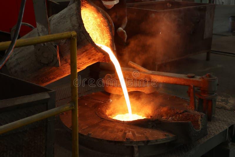 Il ferro fuso versa dalla siviera nel forno di fusione fotografia stock