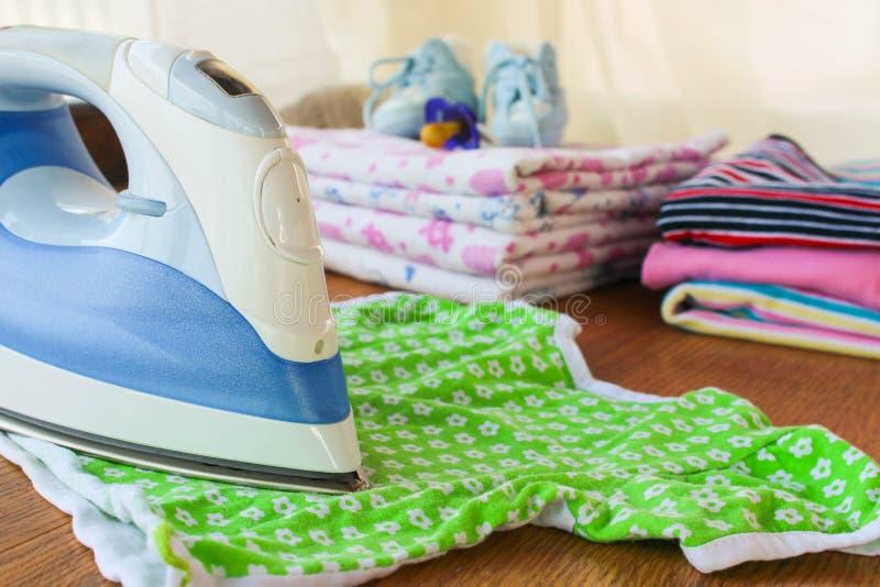 Il ferro segna la maglietta dei bambini Nei precedenti, nei pannolini, nei vestiti del bambino, nella tettarella, nelle piccole s fotografia stock libera da diritti