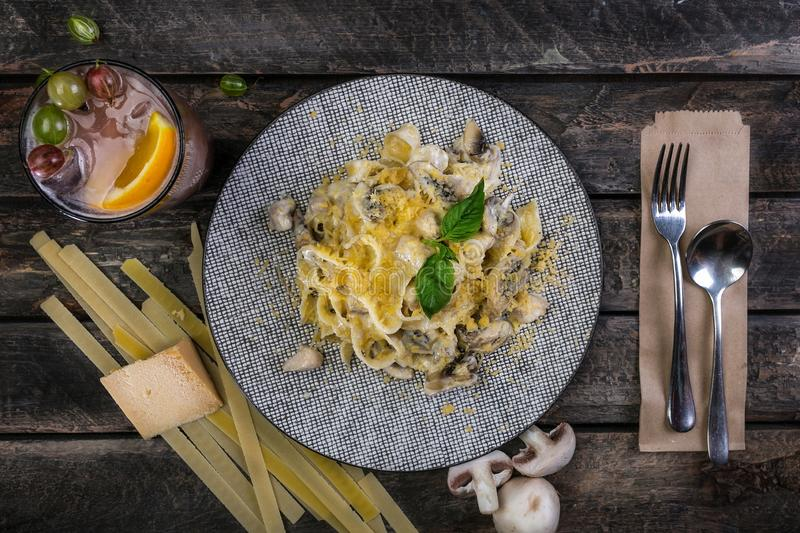 Il fettuccine italiano della pasta con formaggio, pollo e funghi, è servito sul bello piatto ceramico con la coltelleria immagine stock libera da diritti