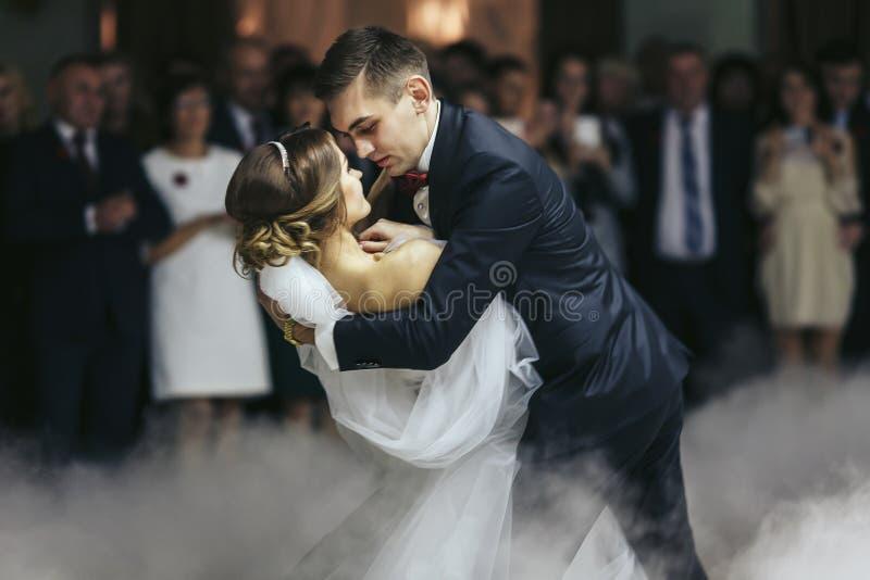 Il fidanzato tiene la sposa in sue mani mentre balla nel fumo fotografia stock libera da diritti