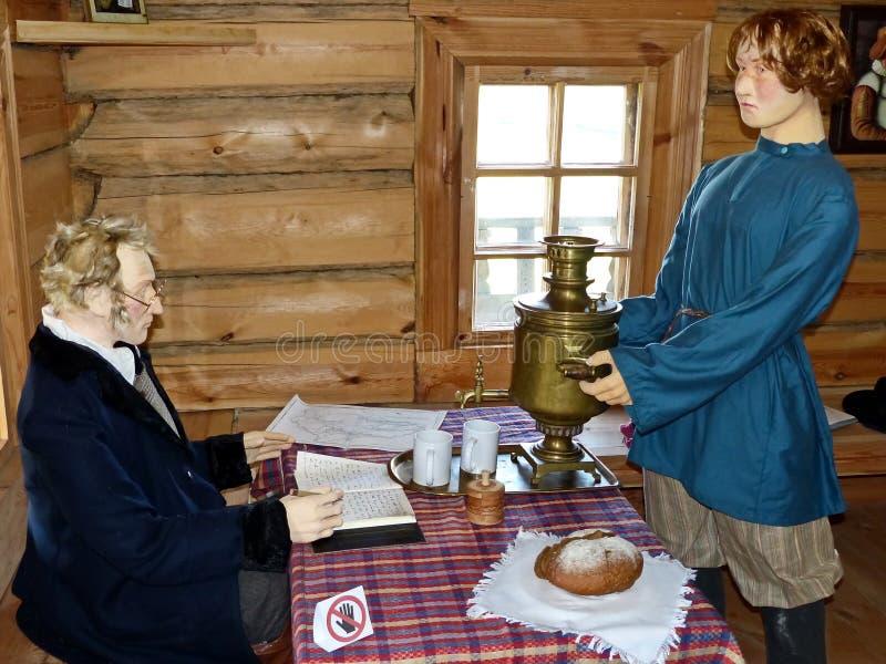 Il figlio più anziano del proprietario porta ad ospiti la samovar Lo scienziato scrive qualcosa in suo diario Alla locanda immagine stock