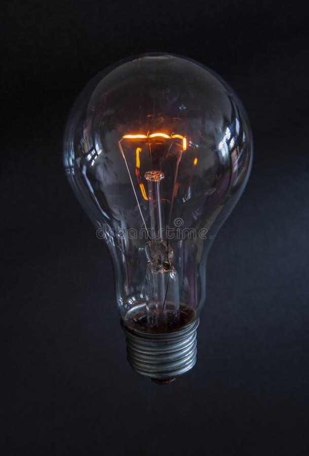 Il filamento in una lampadina di vetro su un fondo scuro fotografia stock