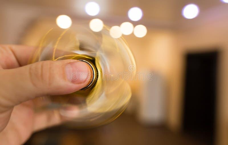 Il filatore dorato sta filando in sua mano fotografia stock libera da diritti