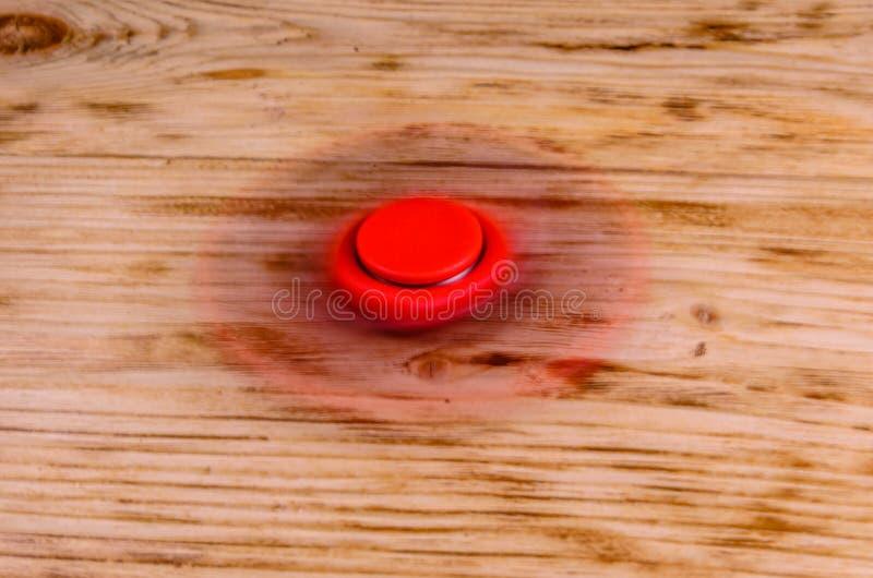 Il filatore rosso di irrequietezza gira sullo scrittorio di legno fotografie stock libere da diritti