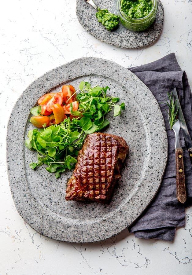 Il filetto arrostito della bistecca di manzo sul piatto di pietra grigio con insalata e il chimichurri sauce immagini stock
