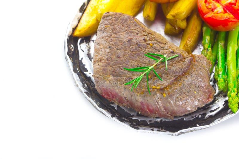 Il filetto di bue arrostito è servito con i pomodori e le verdure dell'arrosto fotografie stock libere da diritti