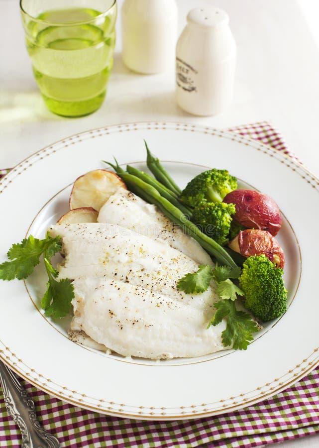 Il filetto di pesce al forno è servito con i broccoli, il fagiolino e la patata fotografia stock libera da diritti