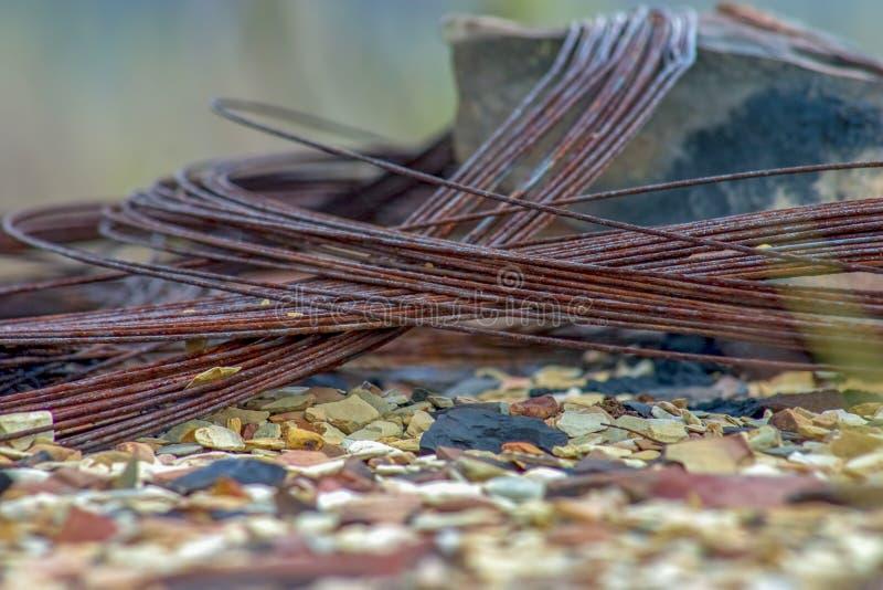 Il filo di ferro arrugginito ha aggrovigliato in una roccia immagine stock libera da diritti