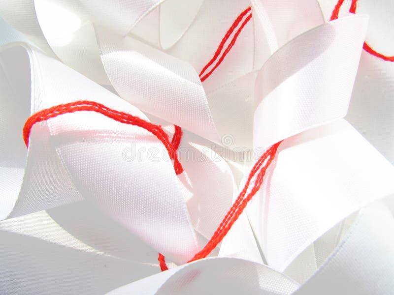 Il filo spesso della lana rossa luminosa ha avvolto un fondo di cucito caotico del latte nastro bianco del raso dell'ampio fotografia stock libera da diritti