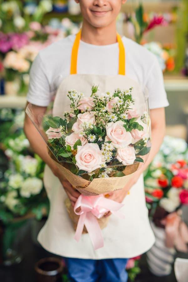 Il fiorista maschio bello sta stando nel negozio di fiore e sta tenendo il bou fotografia stock