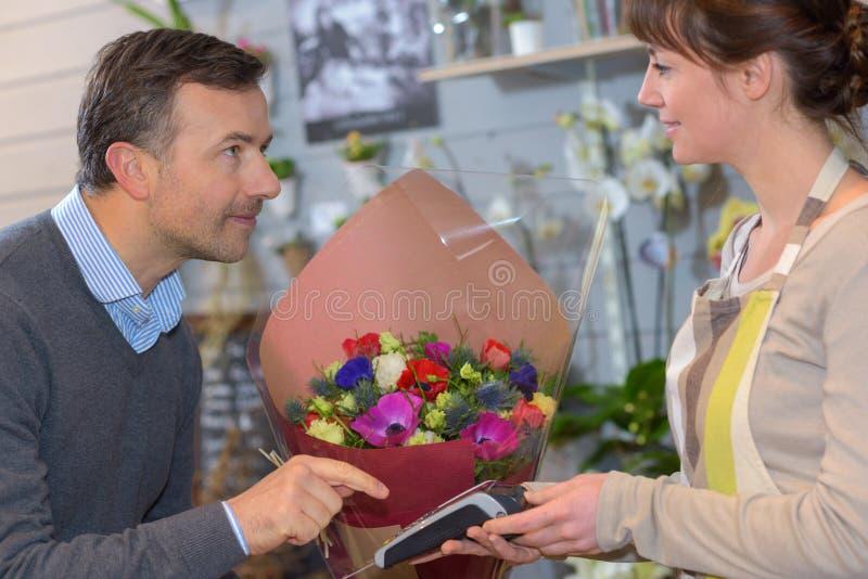Il fiorista serve il cliente maschio quando compra i fiori al deposito fotografia stock