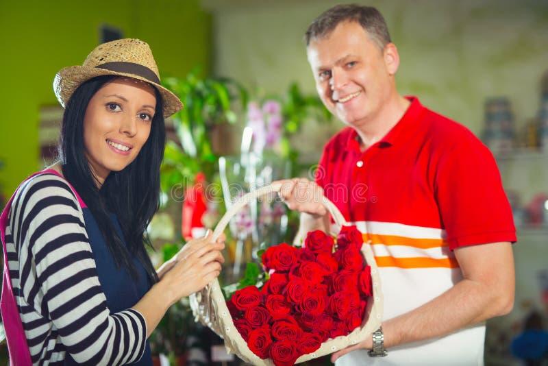 Il fiorista serve il cliente maschio in fiori d'acquisto al deposito fotografia stock