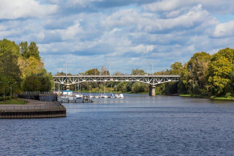 Il fiume di Tvertsa sfocia nel fiume Volga in Tver', Russia Ponte della strada sopra il fiume ed il pilastro della città fotografie stock