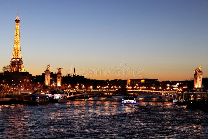 Il fiume la Senna Parigi di notte con il ponte e la torre Eiffel di Alexandre III ha illuminato la Francia fotografia stock libera da diritti