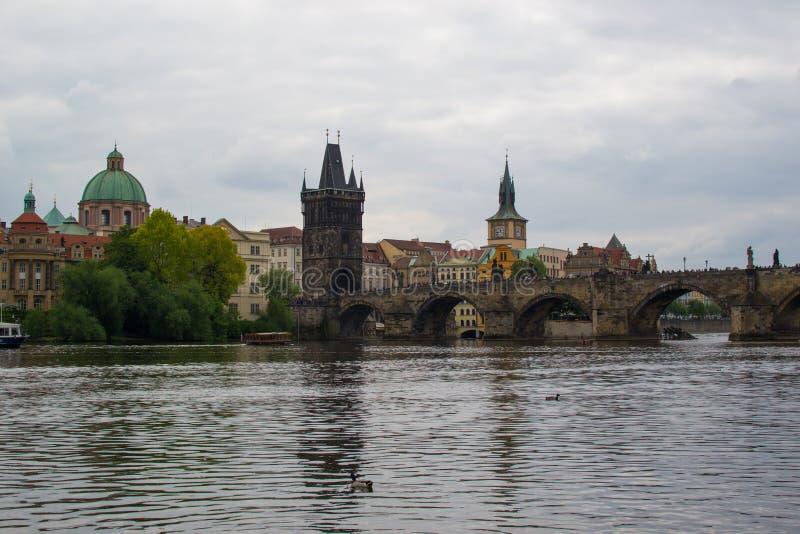 Il fiume Vltava attraversa Praga con Charles Bridge Karl?v most e il ponte vecchio della città Starom?stská mostecká v?ž fotografia stock