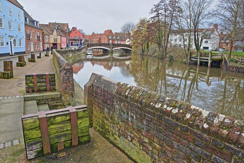 Il fiume Wensum della riva del fiume con le case variopinte ed il ponte di Fye nei precedenti fotografie stock libere da diritti