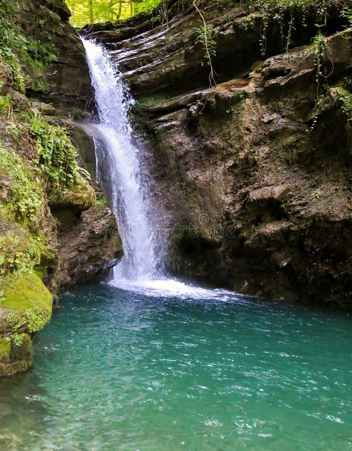 Il flusso veloce dell'acqua una cascata della foresta sfocia nell'acqua calma azzurrata contro una gola di pietra stagionata dell fotografia stock