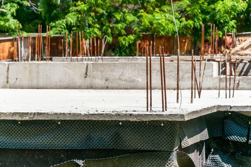 Il fondamento di nuova casa con il calcestruzzo di rinforzo e le barre d'acciaio si chiudono su del cantiere immagini stock libere da diritti