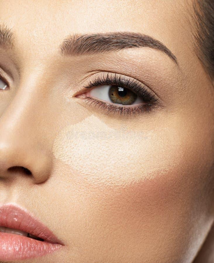 Il fondamento tonale di trucco cosmetico è sul fronte del ` s della donna immagini stock libere da diritti