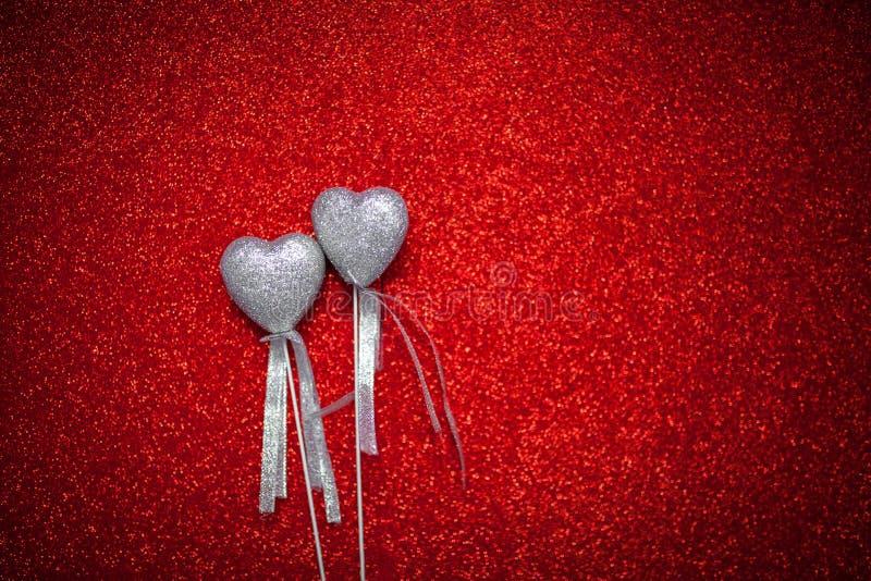 Il fondo brillante rosso con i cuori d'argento, l'amore, il giorno del ` s del biglietto di S. Valentino, struttura il fondo astr fotografia stock
