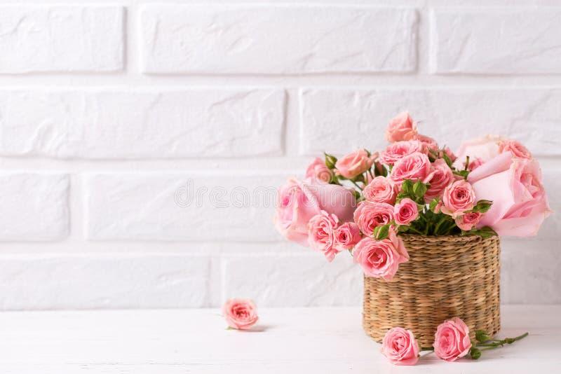 Il fondo con le rose rosa fiorisce contro il muro di mattoni bianco immagine stock