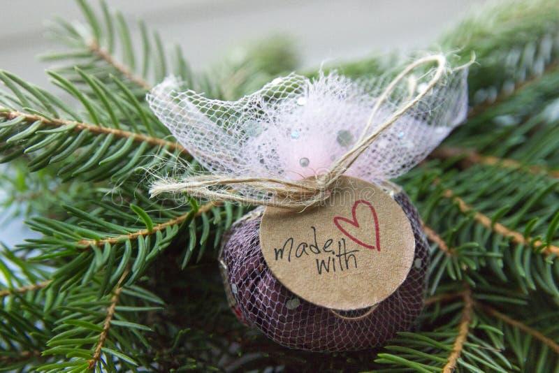 Il fondo dei rami verdi dell'albero di Natale là è un lavoro fatto a mano avvolto regalo fatto con il nuovo anno della carta kraf fotografia stock