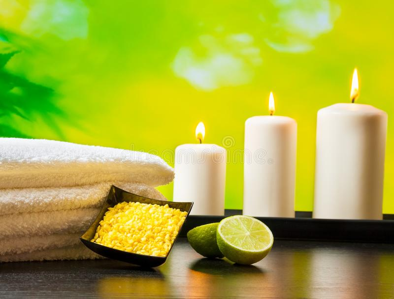 Il fondo del confine di massaggio della stazione termale con l'asciugamano ha impilato le candele e la calce del sale marino fotografia stock