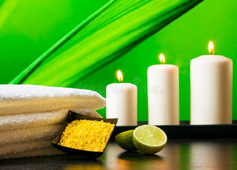 Il fondo del confine di massaggio della stazione termale con l'asciugamano ha impilato le candele e la calce del sale marino fotografie stock