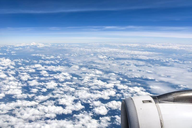 Il fondo della vista il cielo e le nuvole può vedere la superficie della Terra e la montagna dalla finestra dell'aeroplano con lo immagine stock libera da diritti