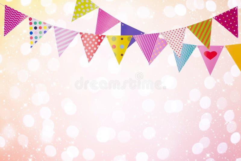 Il fondo di festa con le bandiere variopinte sopra le luci astratte ed emette luce fotografie stock