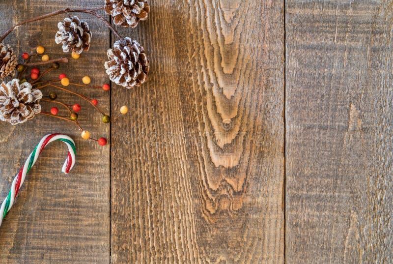 Il fondo di legno rustico della plancia con bianco ha fornito di punta le pigne, berri fotografia stock