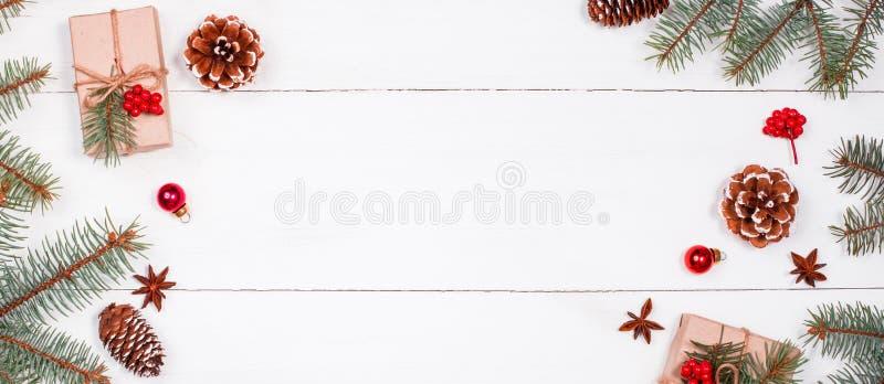 Il fondo di Natale con il regalo di Natale, abete si ramifica, pigne, i fiocchi di neve, decorazioni rosse fotografia stock libera da diritti