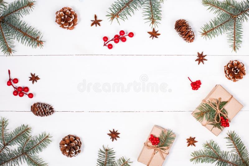Il fondo di Natale con il regalo di Natale, abete si ramifica, pigne, i fiocchi di neve, decorazioni rosse Compositi del buon ann fotografia stock