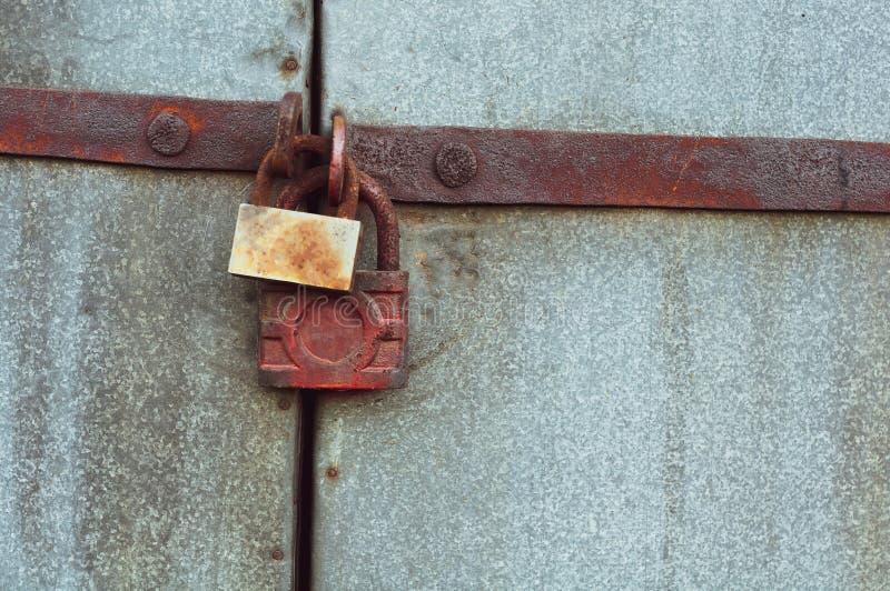 Il fondo di vecchi portoni grigi del metallo si è chiuso su due lucchetti arrugginiti fotografia stock libera da diritti