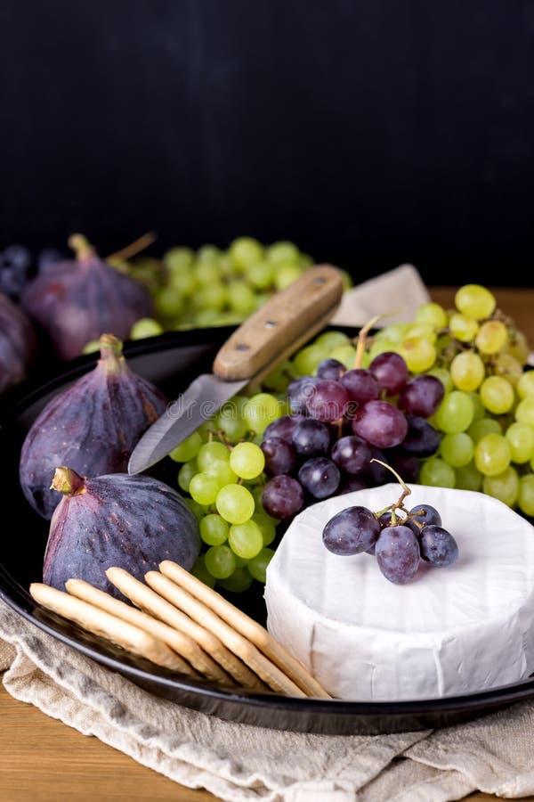 Il formaggio Brie Camembert con i fichi e l'uva sull'alimento di legno della tavola per i fichi del vino verdi ed il piatto del c fotografia stock libera da diritti