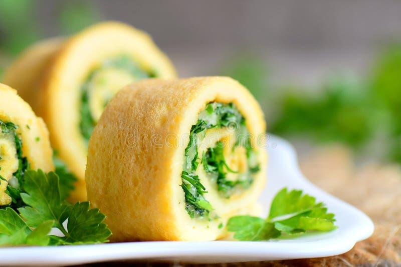 Il formaggio e le erbe casalinghi hanno farcito l'omelette Tagli l'omelette con formaggio grattugiato e le erbe finemente tritate fotografia stock