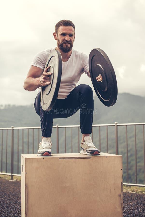 Il forte atleta maschio che fa la scatola salta con due piatti all'aperto sopra la montagna fotografie stock