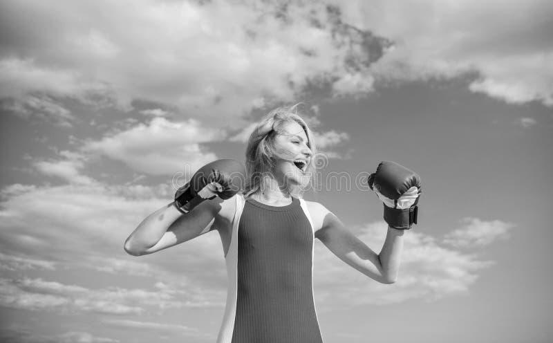 Il forte aumento dei guantoni da pugile della donna passa il fondo del cielo blu Lotta di simbolo dei guantoni da pugile della ra fotografia stock libera da diritti