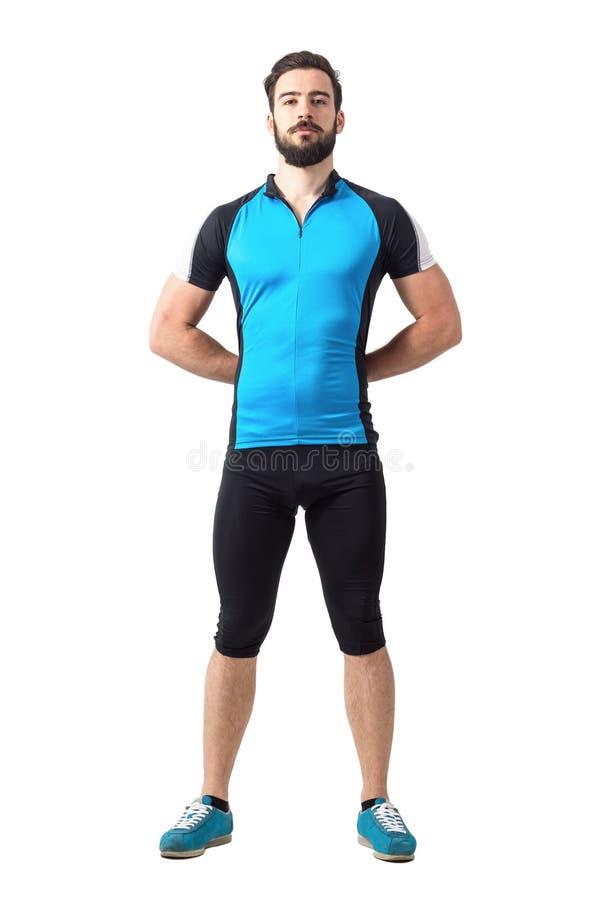 Il forte ciclista sportivo fiero nel riciclaggio copre la condizione con le mani delle mani dietro indietro fotografia stock libera da diritti