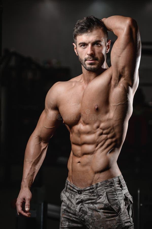 Il forte e giovane atletico bello muscles l'ABS ed il bicipite immagine stock libera da diritti