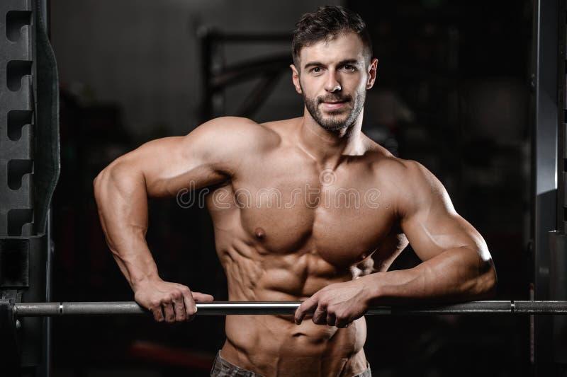 Il forte e giovane atletico bello muscles l'ABS ed il bicipite immagini stock libere da diritti