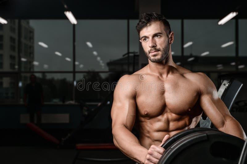 Il forte e giovane atletico bello muscles l'ABS ed il bicipite fotografia stock libera da diritti