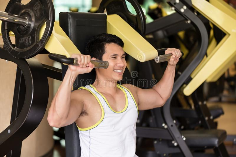 Il forte giovane che si esercita per le armi muscles ad un club di forma fisica w immagini stock