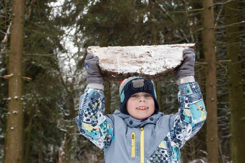 Il forte giovane solleva il pezzo di legno pesante e lo tiene fotografia stock
