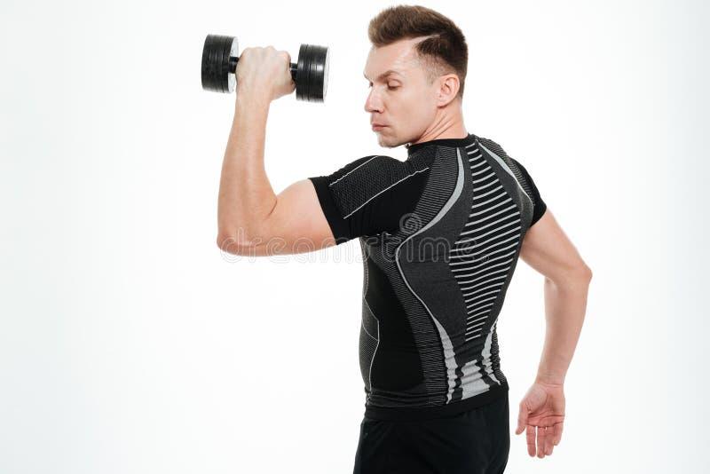 Il forte sportivo bello fa gli esercizi di sport con la testa di legno immagini stock libere da diritti