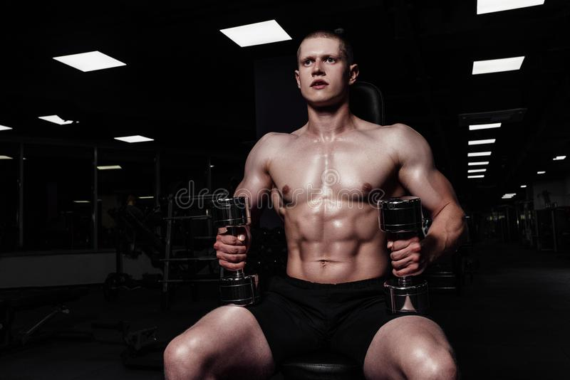 Il forte uomo atletico bello che pompa su muscles con le teste di legno Culturista muscolare con il torso nudo di sport che fa gl fotografia stock